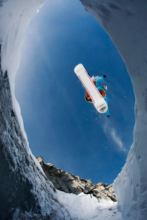 View from below of agile snowboarder in high jump over blue sky photo