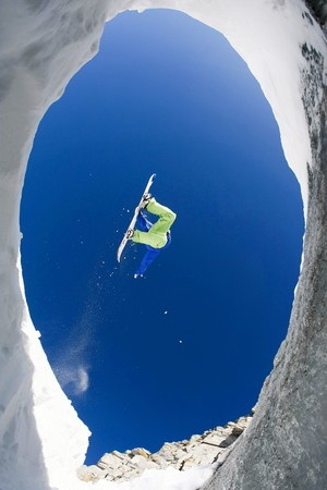 Below view of fearless sportsman jumping high over snow covered mountains on snowboard photo