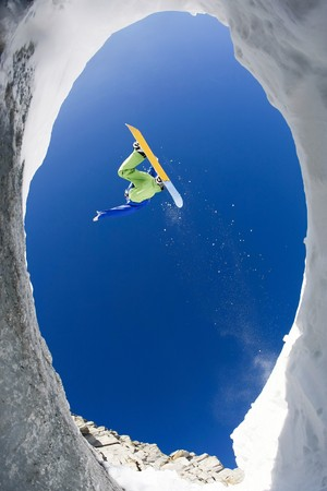ниже: View from below of excited snowboarder leaping over mountainside and taking pleasure in it Фото со стока