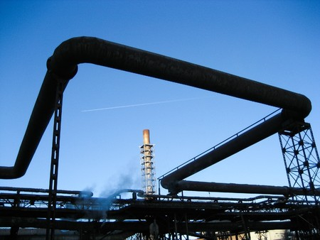 Image of pipes of large modern factory on bakckground of blue sky and other constructions photo