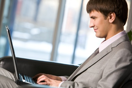 Photo of successful manager typing on laptop and looking at its screen photo