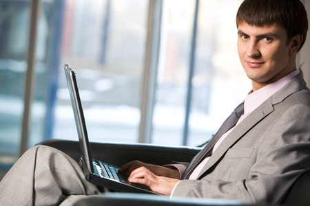 Handsome male typing on keyboard of laptop and looking at camera photo