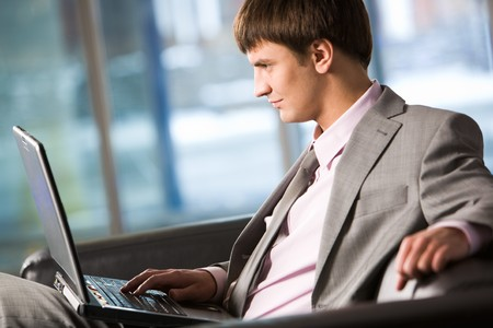 Photo of smart businessman working on laptop in office  photo