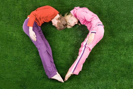 Shape of heart made up by guy and girl lying on green grass Stock Photo - 4252527