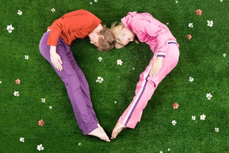 Heart formed by sleeping couple lying on green meadow photo