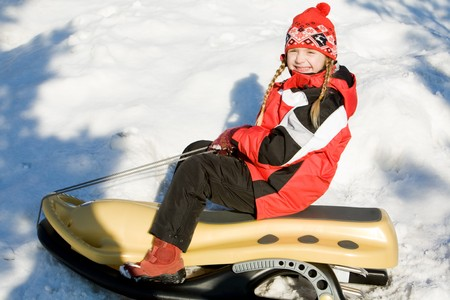 Portrait of smiling girl sitting on the sledge in the forest  photo