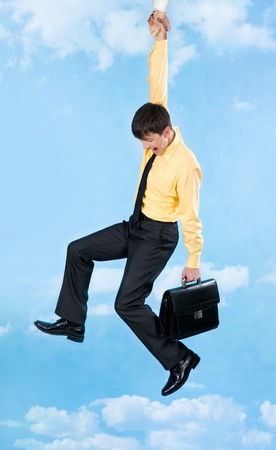 Vertical image of businessman in trouble holding at helping hand on background of sky Stock Photo - 4252454