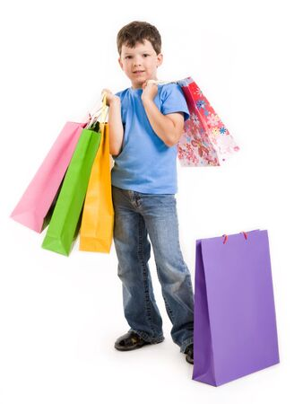 shoppings: Image of smiling boy holding bags with presents or shoppings looking at camera Stock Photo
