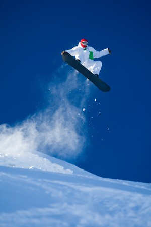 snowboarder jumping: Photo of brave sportsman jumping on snowboard over blue sky Stock Photo