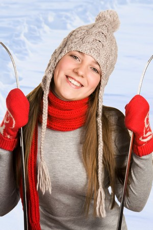 Portrait of smiling female holding skis with snowdrift at background photo