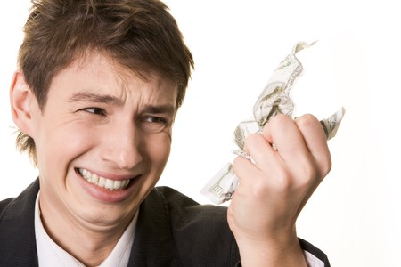 Anxious guy looking annoyingly at crumpled dollar note in his hand  Stock Photo - 4321305