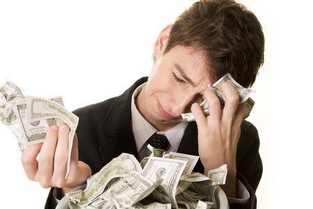 Conceptual image of grieving young businessman over heap of crumpled dollars Stock Photo - 4321310