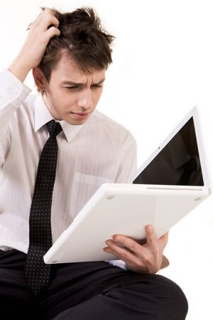 Portrait of puzzled businessman looking into open laptop photo