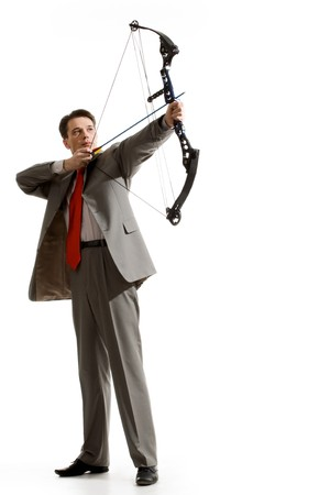 Portrait of courageous businessman holding crossbow and aiming at target photo