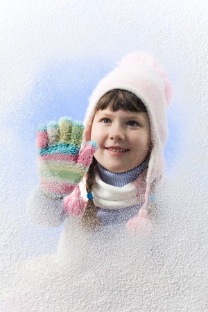 Image of cute girl looking through window on winter day photo