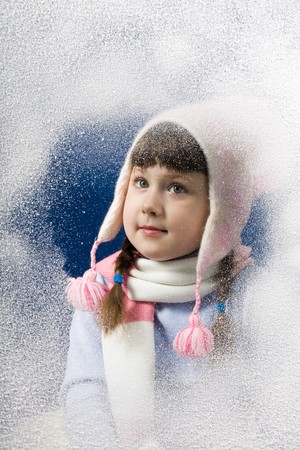 flurry: Photo of pretty little girl behind frosted window looking through it