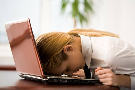 Image of very tired businesswoman or student putting her face on keyboard of laptop Stock Photo - 4321249