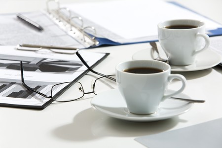 coffe break: Close-up of glasses, documents, pen, cups of coffee on the table
