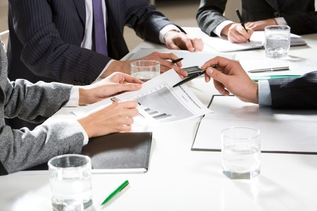 Human hands holding pens and papers, making notes in documents, touching the phone during business meeting  Stock Photo