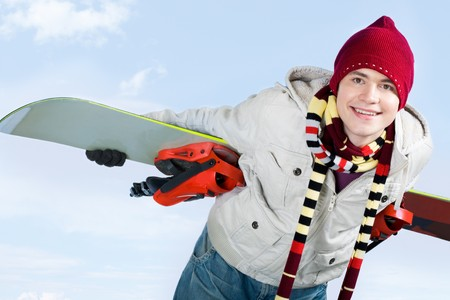 skillful: Photo of skillful teenager with snowboard behind his back over blue background