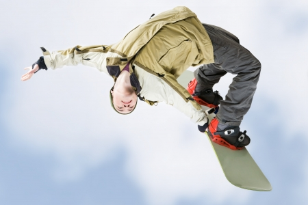 snowboarder jumping: Image of courageous guy jumping on snowboarder in the air
