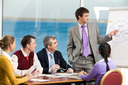 Image of business group listening attentively to their young colleague making presentation on board photo