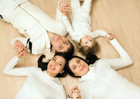 Above view of family members lying on the floor and holding each other by hands photo