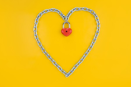 Image of metallic heart made of chain with lock on a yellow background  photo