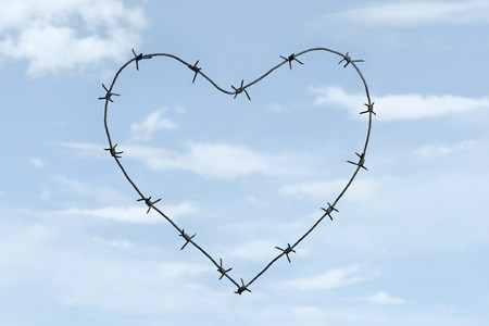 Creative image of heart shape made of barbed wire over blue sky background Stock Photo - 4322717