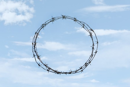 Photo of thorny wreath made of barbed wire on background of blue sky photo