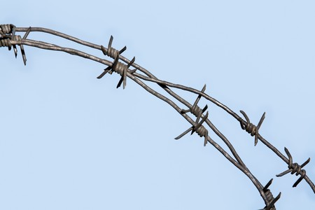 Part of barbed wire with blue sky on background photo