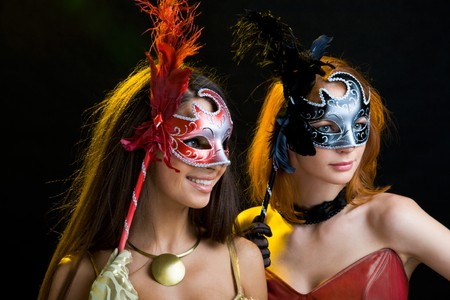 Portrait of beautiful women in masks over black background photo