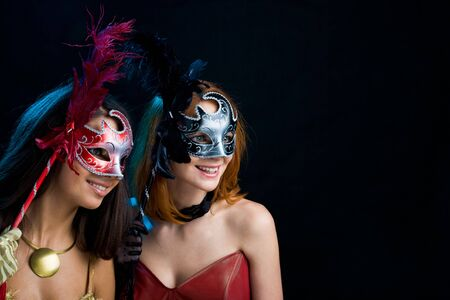 Portrait of attractive ladies holding carnival masks and looking through them photo