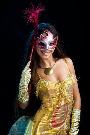 Portrate of elegant woman in yellow apparel with venetian mask in hand photo