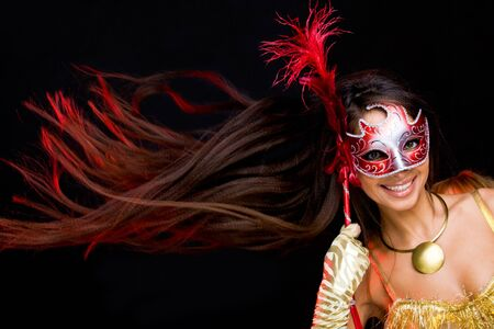 Portrait of pretty female looking through decorative mask on black background photo