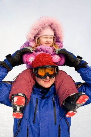 Portrait of sportsman wearing sunglasses and holding his daughter on neck in winter photo