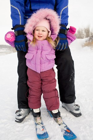 Portrait of cute girl wearing winter clothes while skiing with her father photo