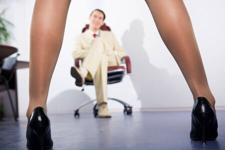 apart: Photo of feminine legs in high heeled shoes with sitting businessman at background