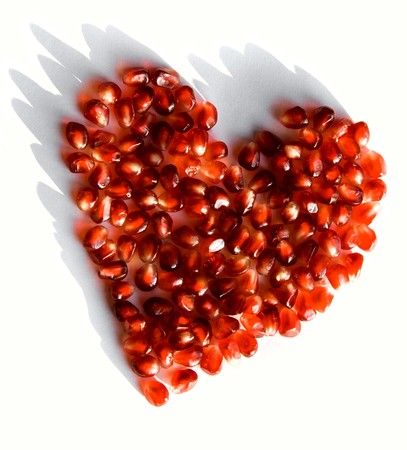 Creative photo of red heart made up of pomegranate seeds