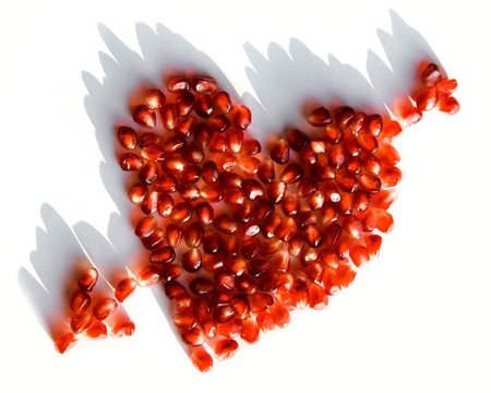 Image of pomegranate heart pierced by arrow over white background photo