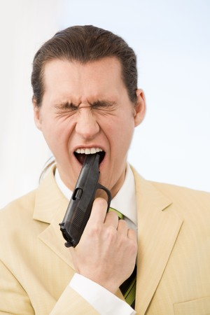 Portrait of scared young businessman putting gun into his mouth photo