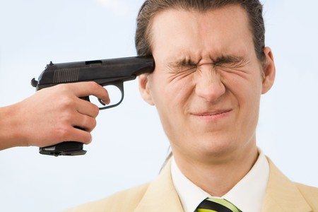 Frustrated businessman being scared while having revolver at his temple photo