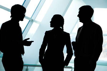 Drie silhouetten van zakenlui interactie met elkaar in het kantoor
