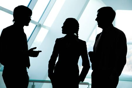 three: Three silhouettes of businesspeople interacting with each other in the office Stock Photo
