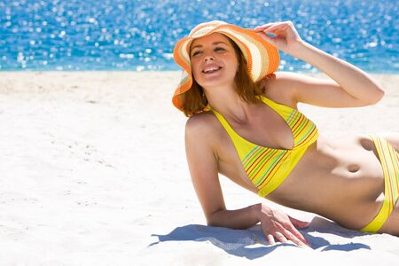 Image of luxurious woman in bikini and hat relaxing on the seashore on hot day