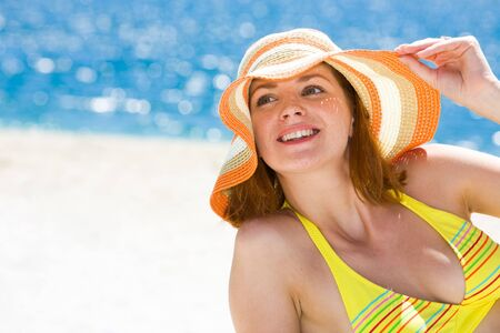 Portrait of happy woman in hat enjoying hot summer day on the beach photo