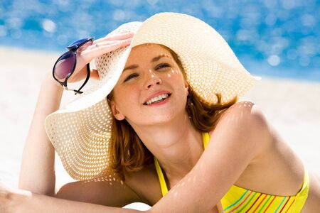Photo of resting woman in hat holding sunglasses and sunbathing photo