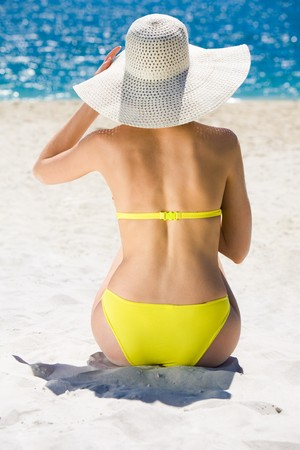 Rear view of young slim woman wearing swimwear and hat sitting on sandy beach photo