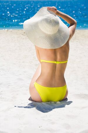 Back view of beautiful woman sitting on seashore and sunbathing photo