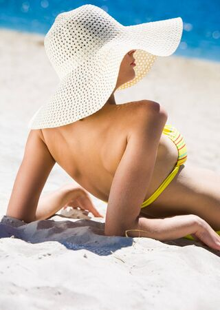 Image of relaxing female in big hat elbowing on sand while sunbathing photo